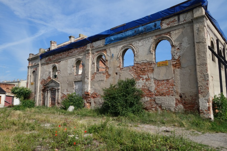 What's left of the Żychlin synagogue. Note the windows used to extend much father down, and the more recent doorway (now blocked) added when the building was used as a warehouse. The weedy area in the foreground used to be a fenced garden.