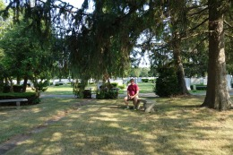My brother Chris resting on a commemorative bench at the family burial plot.