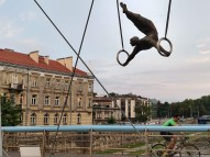 A biker pedals by a sculpture of an acrobat suspended on wires, historic Podgórze in the distance.
